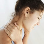 Young Woman Holding Her Neck in Pain --- Image by © Royalty-Free/Corbis